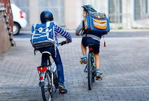 Två skolpojkar med hjälm och ryggsäck cyklar bort från kameran. Foto.
