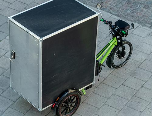 Trehjulig grön paketcykel med stor grå låda bakpå. Foto.