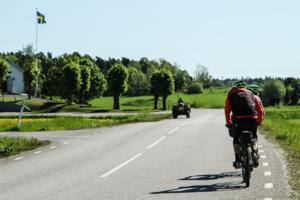 Två cyklister på landsväg möter en traktor.